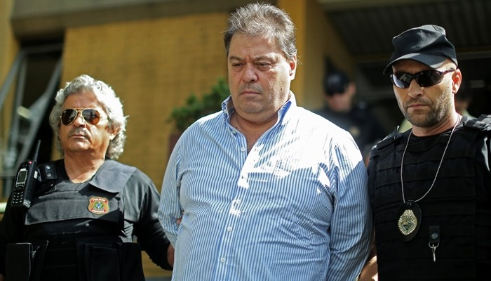 Former senator Gim Argello is escorted on April 13, 2016 as he arrives at the Forensic Medicine Institute in Curitiba, after being arrested in Brasilia-DF.  Former senator Gim Argello is one of the targets of the 28th stage of the operation Lava Jato.  / AFP / Heuler Andrey